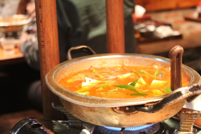 A delicious, steaming cauldron full of spicy kimchi jigae.